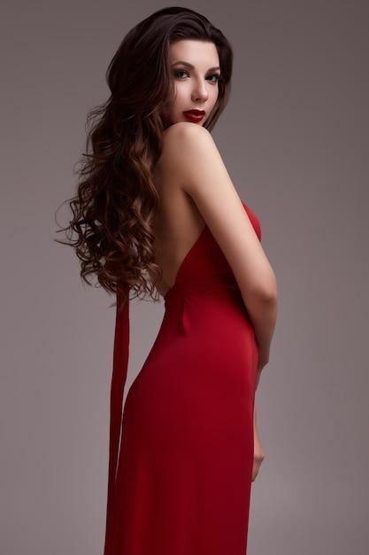 Superbe jeune femme brune aux cheveux bouclés en robe rouge Photo Premium