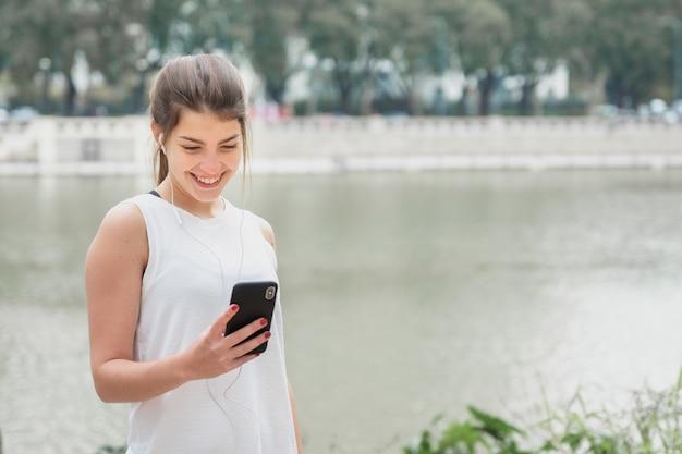 Superbe jeune femme vérifiant son téléphone Photo gratuit