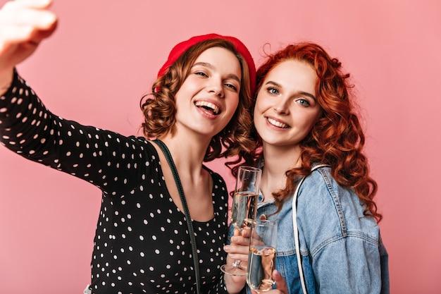Superbes Filles Buvant Du Champagne Avec Le Sourire. Photo De Studio D'adorables Jeunes Femmes Tenant Des Verres à Vin Sur Fond Rose. Photo gratuit