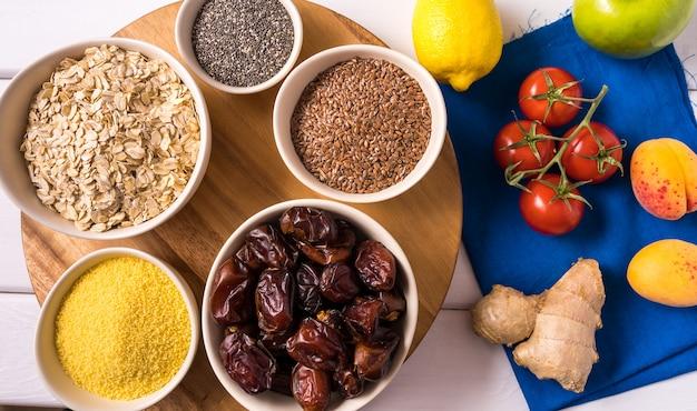 Superfoods dans des bols, des légumes frais sur du bois blanc. Photo Premium