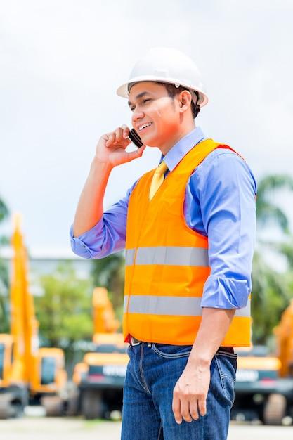 Superviseur asiatique téléphonant sur un chantier de construction Photo Premium