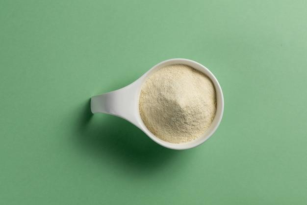 Supplément de bodybuilding sportif de poudre de protéine de lactalbumine. vue de dessus de cuillère en porcelaine blanche avec poudre à saveur de vanille. couleur unie: vert Photo Premium