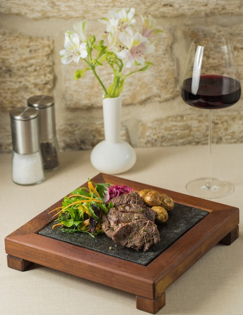 Un support en bois de steak et de pommes de terre avec une salade de verdure Photo gratuit