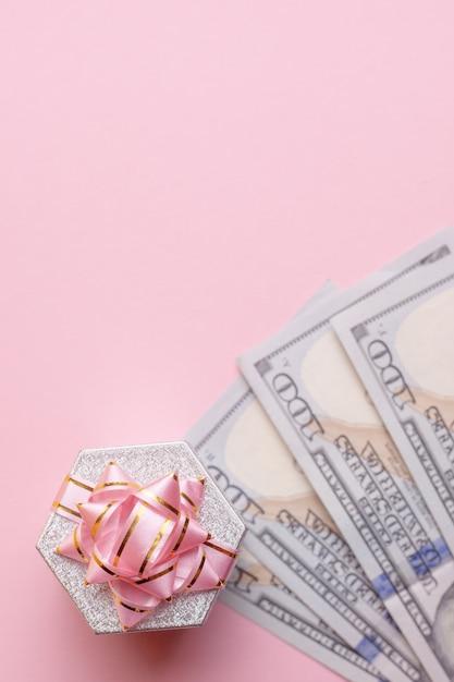 Support de boîte cadeau sur dollars en argent sur fond rose. Photo Premium