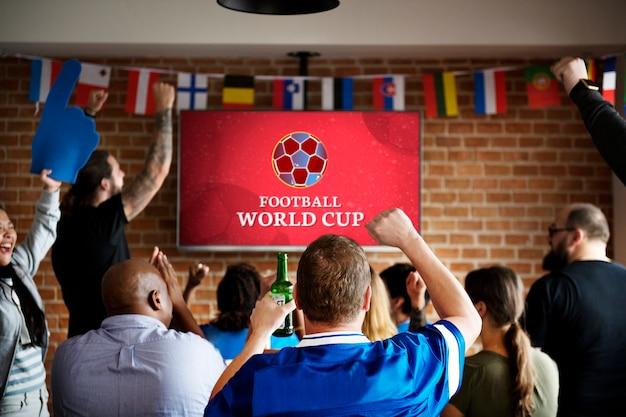 Des supporters enthousiastes regardant un match de football au pub Photo Premium