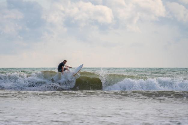 Un avec un surf dans ses mains au bord de la mer Photo Premium