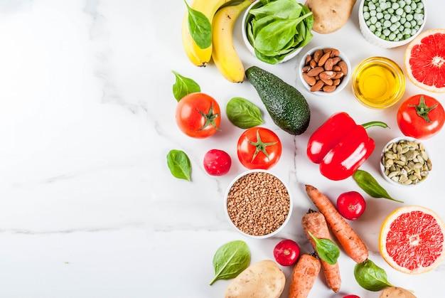 Surface alimentaire saine, produits de régime alcalins à la mode - fruits, légumes, céréales, noix. huiles, surface en marbre blanc au-dessus Photo Premium