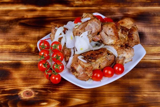 Sur la surface en bois du plateau se trouve un shish kebab, un barbecue. Photo Premium