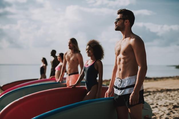 Surfers en maillots de bain debout à la plage, Photo Premium