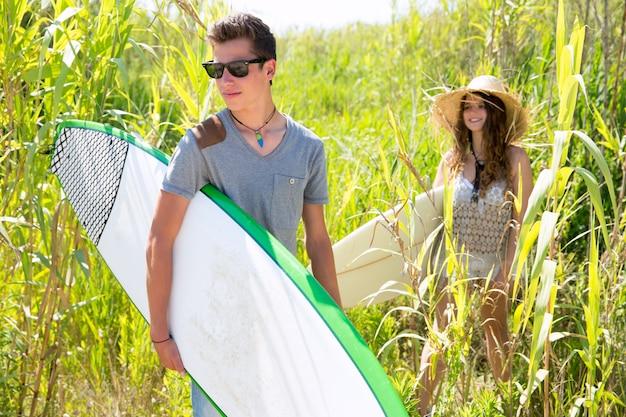 Surfeur garçon et fille marchant dans la jungle verte Photo Premium