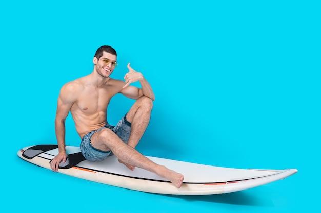 Surfeur Homme Posant Montrant Appelez-moi Signe Photo gratuit