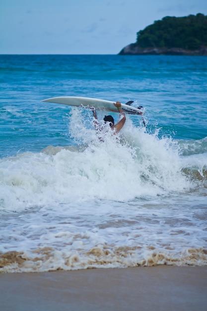 Surfeur transportant la planche de surf à la plage Photo gratuit