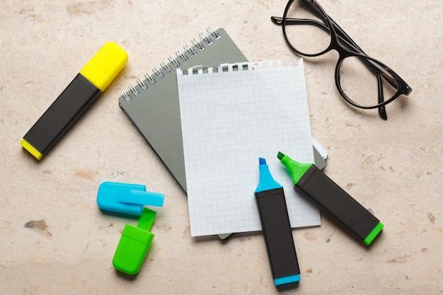 Surligneurs bleus et verts sur une feuille de papier vierge pour bloc-notes posée sur un bureau Photo Premium