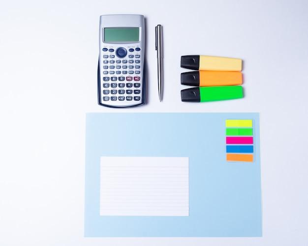 Surligneurs colorés, stylo, marqueurs, calculatrice et papier vierge pour travailler ou étudier Photo Premium