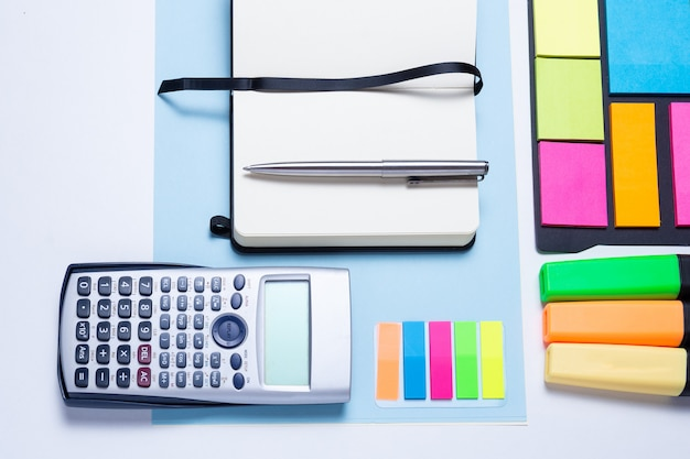 Surligneurs colorés, stylos, marqueurs, calculatrice, cahier et papier vierge pour travailler ou étudier Photo Premium
