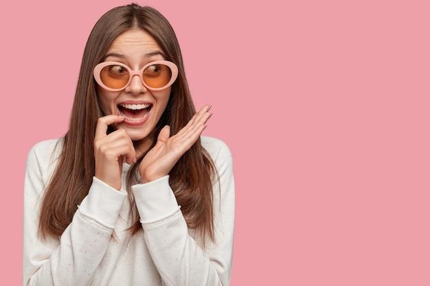 Surpris Belle Jeune Femme Aux Cheveux Noirs, Porte De Grandes Nuances à La Mode, Sourit Largement à La Caméra Photo gratuit