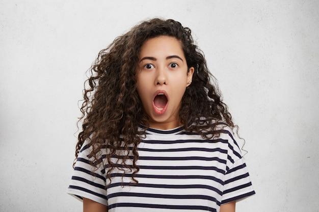 Surpris Femme Excitée Avec Des Cheveux Bouclés Regarde La Caméra, Ouvre Largement La Bouche, étant Choquée Photo gratuit