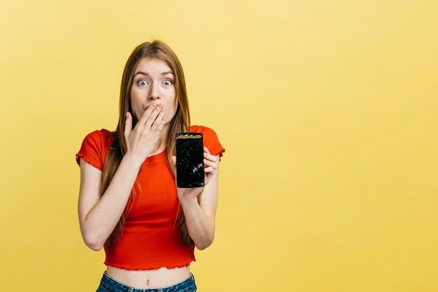 Surpris femme tenant un téléphone cassé avec espace de copie Photo gratuit