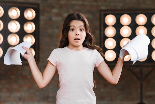 Surpris fille debout devant la lumière de la scène tenant des scripts Photo gratuit