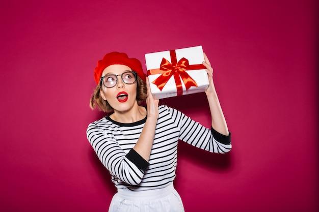 Surpris Gingembre Intrigué Femme à Lunettes Tenant Boîte-cadeau Près De L'oreille Et Regardant Au-dessus De Rose Photo gratuit