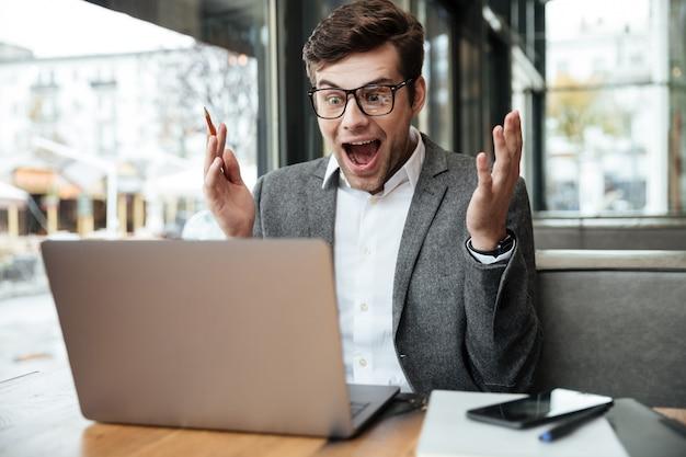 Surpris Homme D'affaires Qui Criait à Lunettes Assis Près De La Table Dans Le Café Et à La Recherche D'ordinateur Portable Photo gratuit