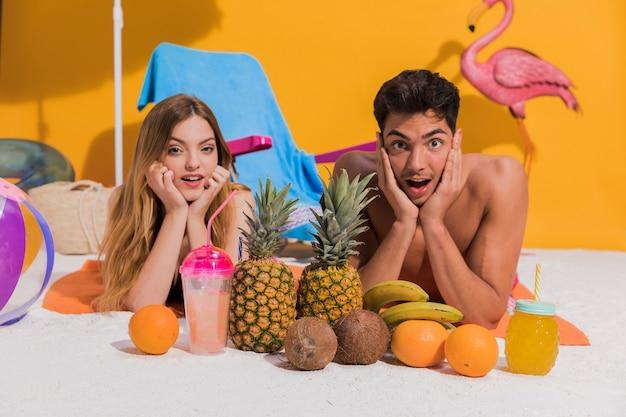 Surpris jeune couple en maillot de bain reposant sur le sable en studio Photo gratuit