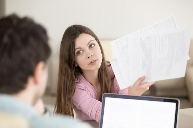 Surpris jeune femme montrant des papiers à l'homme avec loo interrogatif Photo gratuit