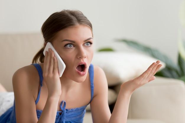 Surpris de jeune femme parlant au téléphone mobile Photo gratuit