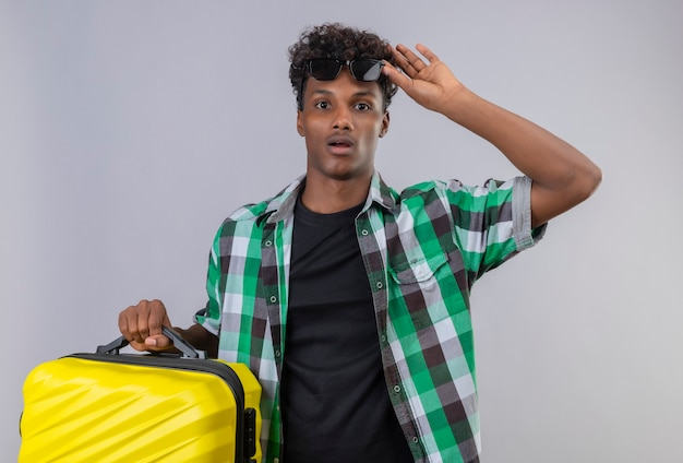 Surpris Jeune Homme Afro-américain Voyageur Tenant Valise Décollant Des Lunettes De Soleil D'étonnement Debout Photo gratuit