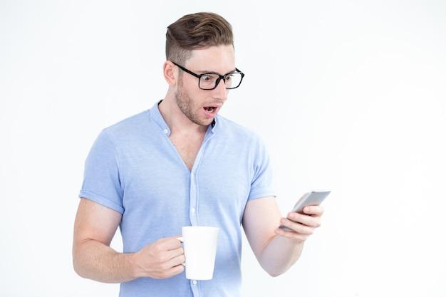 Surpris, jeune homme, lunettes, utilisant, smartphone Photo gratuit