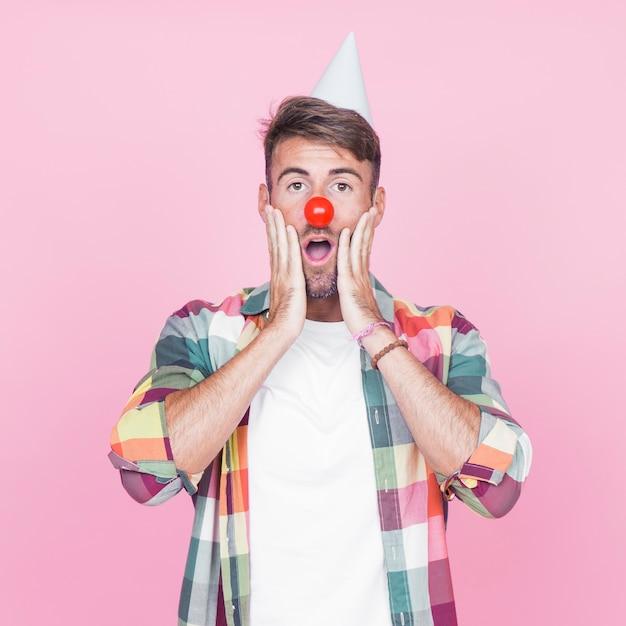 Surpris jeune homme avec nez de clown rouge debout sur fond rose Photo gratuit