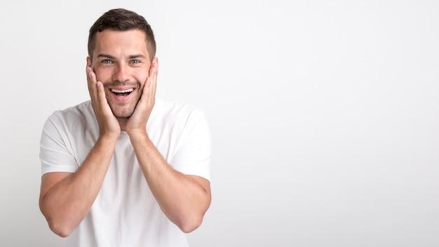 Surpris jeune homme regardant la caméra debout contre un mur blanc Photo gratuit