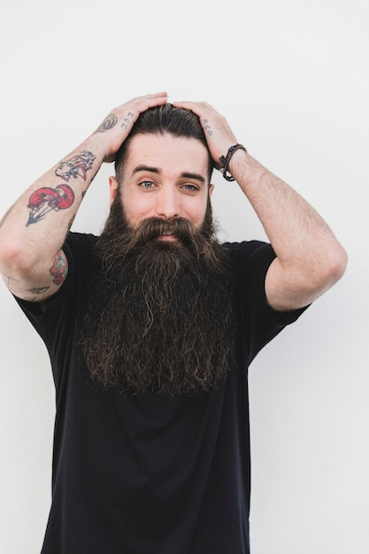 Surpris jeune homme tatoué debout contre une surface blanche Photo gratuit