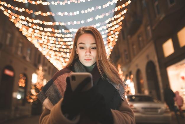 Surpris Jolie Fille Se Tient Dans La Rue, Tient Un Smartphone Dans Ses Mains Et Regarde Avec émotion Sur L'écran Dans Le Contexte Des Décorations De Lumières De La Ville Photo Premium