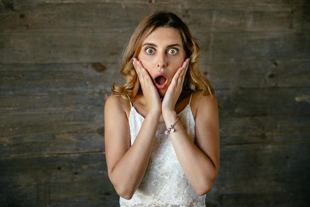 Surpris jolie jeune femme choqué de quelque chose, gardant la bouche ouverte Photo gratuit