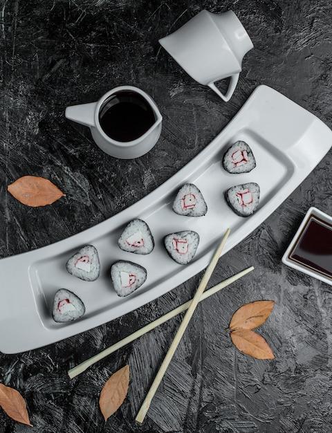 Sushi noir avec sauce dans l'assiette Photo gratuit