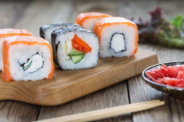 Sushi Roule Sur Une Planche à Découper Avec Du Gingembre Et Des Herbes. Bois Naturel Photo Premium