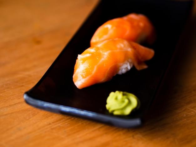Sushi de saumon au wasabi sur une plaque noire Photo gratuit