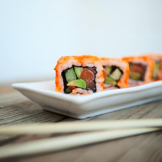 Sushi savoureux avec des baguettes Photo Premium