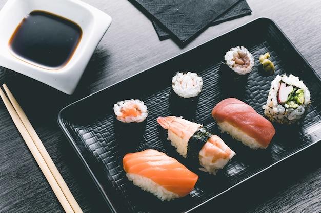 Sushi sur la table en bois. restaurant japonais élégant. style rétro Photo Premium