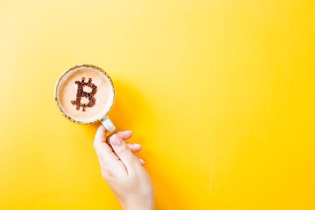 Symbole de la crypto monnaie bitcoin sur une tasse de café sur fond jaune Photo Premium