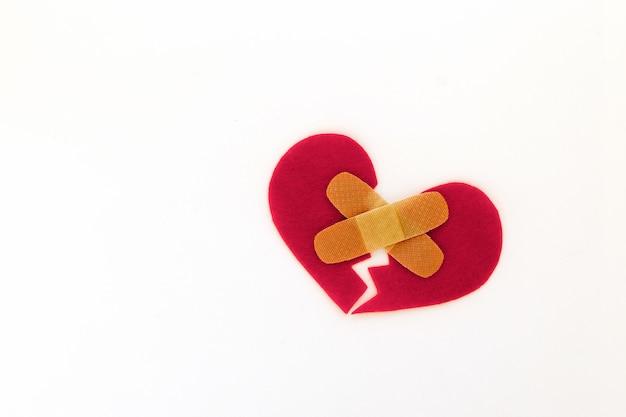 Symbole du coeur rouge brisé avec patch médical sur fond blanc, concept de l'amour Photo Premium