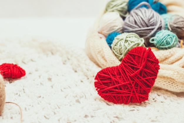 Symbole du coeur tricoté et pelotes de laine Photo Premium