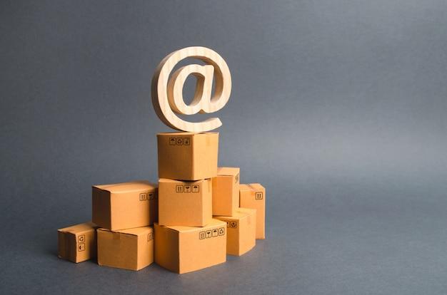Le symbole du courrier électronique at est sur une pile de boîtes en carton. commerce électronique Photo Premium