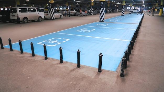 Symbole international pour handicapés peint en bleu vif sur une place de parking du centre commercial. Photo Premium
