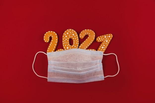 Symbole De Pandémie De Coronavirus De Masque De Protection Avec Des étincelles Festives Et Des étoiles Sur Fond Rouge Photo Premium