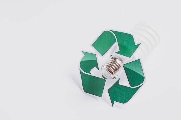 Symbole de recyclage sur ampoule fluorescente compacte isolée sur fond blanc Photo gratuit