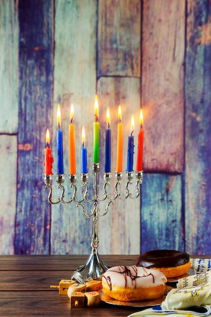 Symboles de la fête juive de hannukah - menorah, beignets, pièces de monnaie et dreidels en bois. Photo Premium