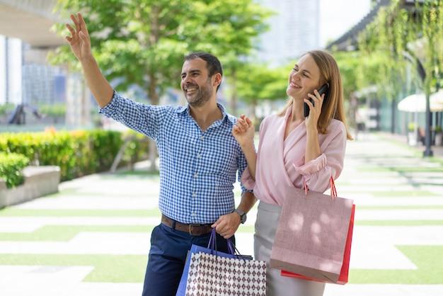 Sympathique couple élégant de clients saluant quelqu'un dans la rue. Photo gratuit