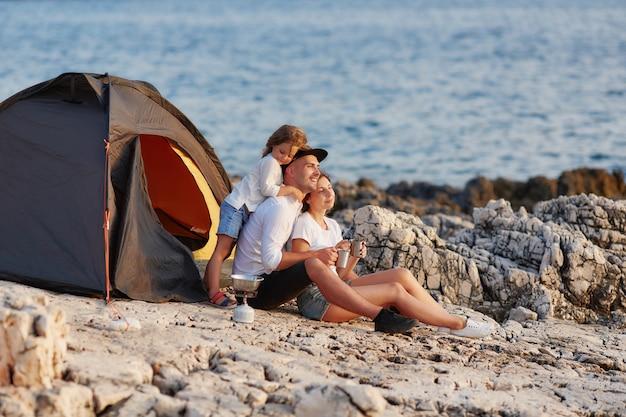 Sympathique famille sincère au repos sur une plage rocheuse près de la tente. Photo Premium